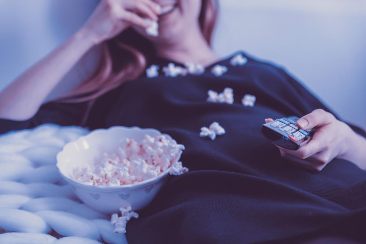ポップコーンを食べながらテレビを見る女性