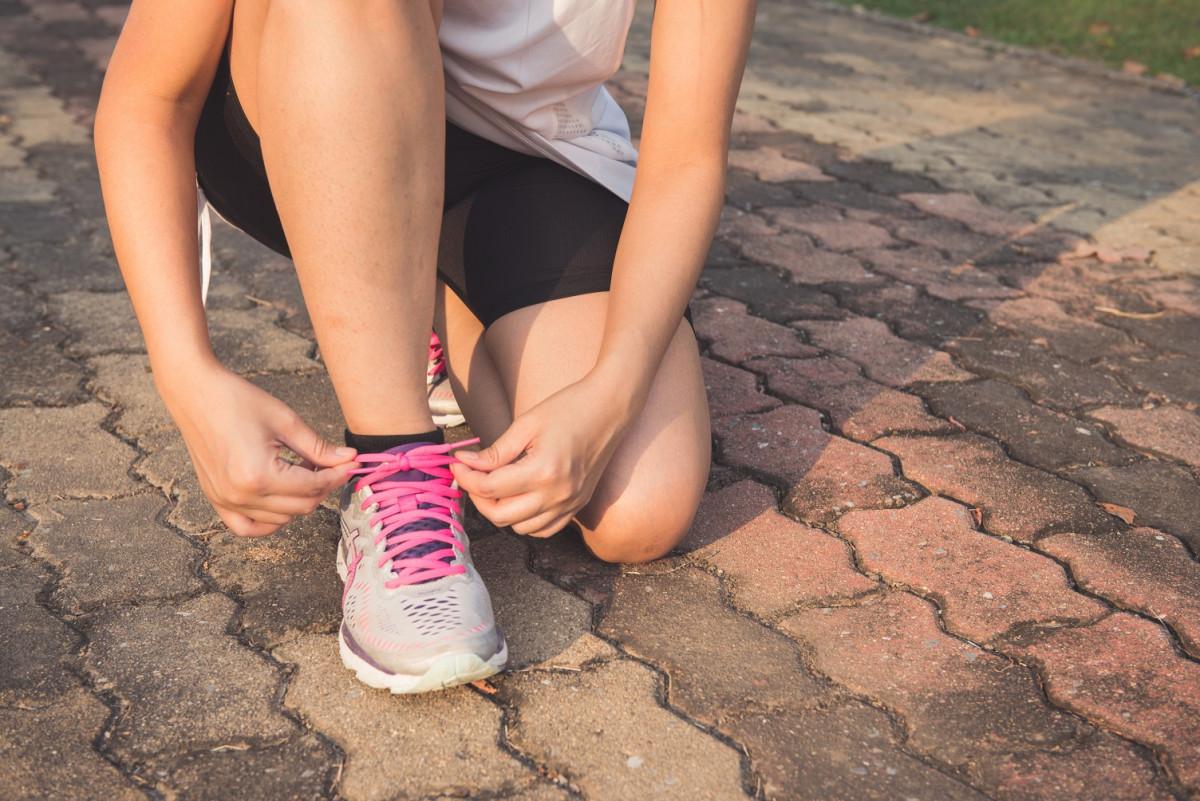 ランニングシューズの靴紐を結ぶ女性
