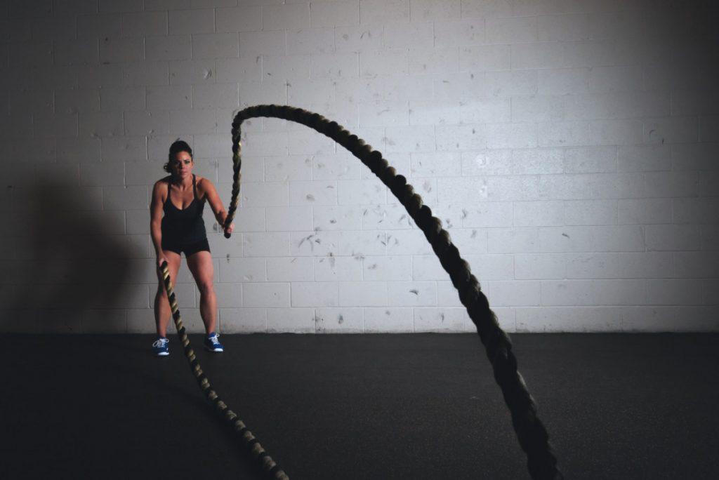 バトルロープでトレーニングする女性