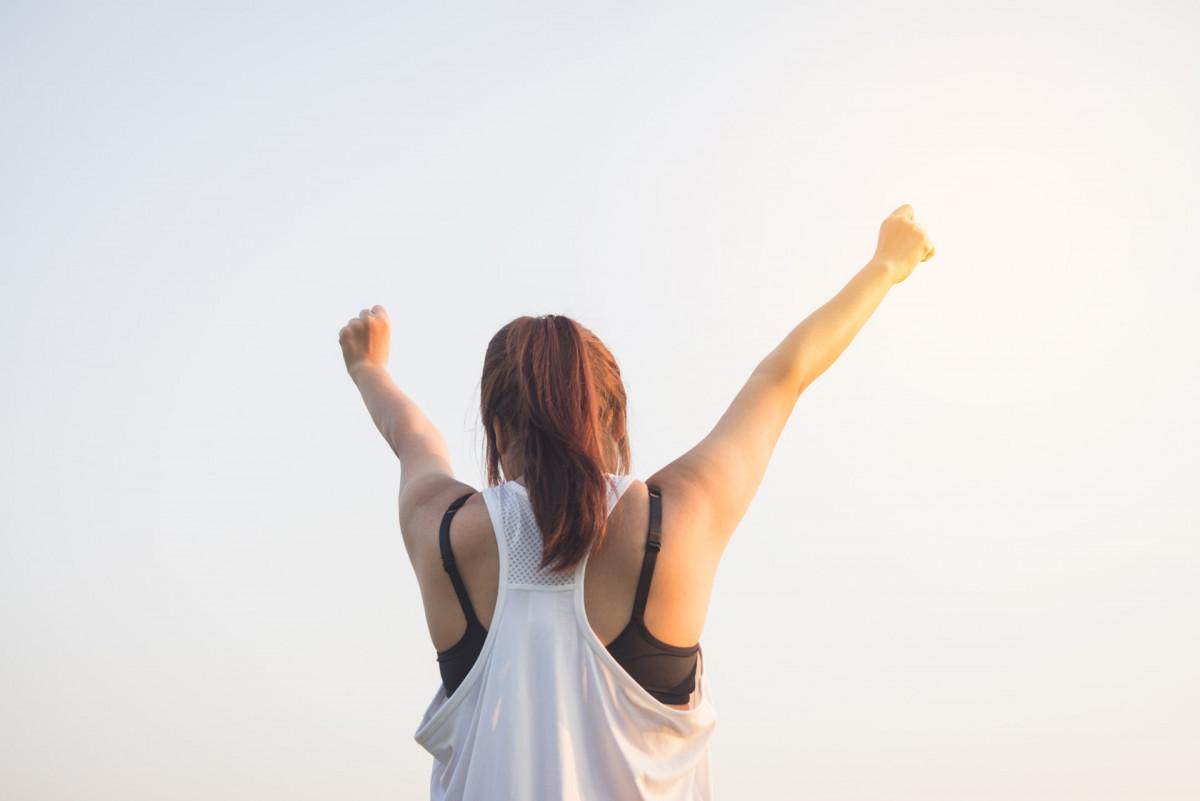 両手を挙げている女性