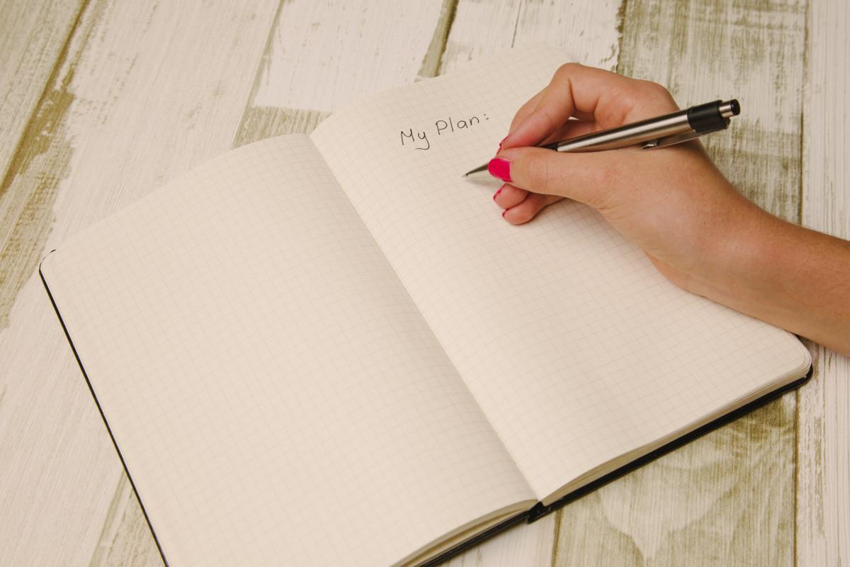 プランをノートに書く女性